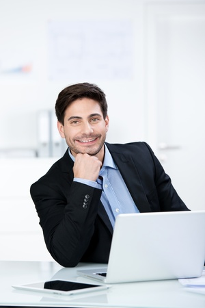 Smiling confident businessman in the office sitting at his desk with his chin on his hand in front of a laptop computer photo