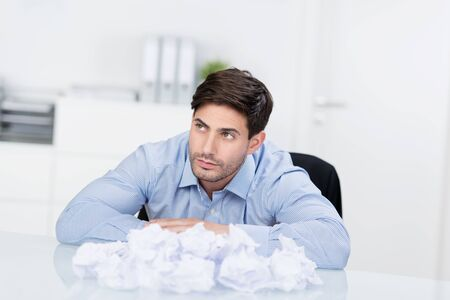writers block: Young handsome businessman sitting at desk with crumpled papers Stock Photo