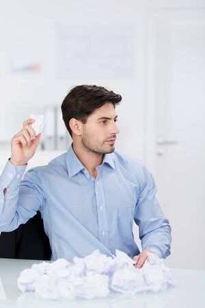lacking: Sitting businessman throwing crumpled paper away at the office