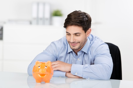 Smiling handsome businessman sitting at desk and looking at the piggybank photo
