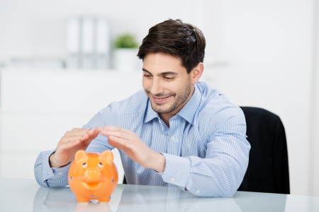 investing: Conceptual portrait of happy young businessman covering piggybank