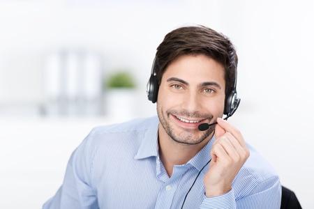 relaciones publicas: Hombre de negocios feliz con los auriculares y el micrófono dentro de la oficina