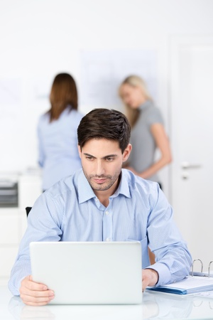Serious businessman concentrating on his work sitting at his desk reading the screen of his laptop while his colleagues work in the background Stock Photo - 21243139
