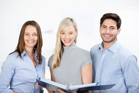 Three attractive young successful business colleagues working as a team discussing a large binder of paperwork smiling at the camera photo