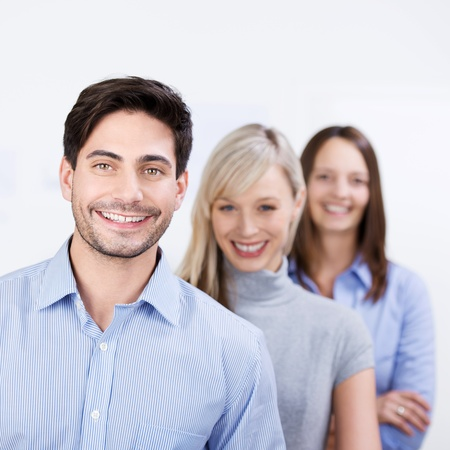 staggered: Business colleagues at work standing in a staggered line smiling confidently at the camera with a handsome young man in the foreground