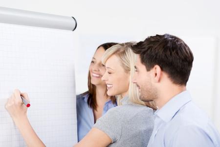 Equipo de negocios la planificación de una estrategia de pie juntos en frente de una pizarra con una mujer a punto de escribir en la página en blanco con un marcador