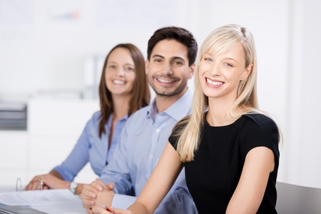 competent: Successful business team in the office seated in a receding row smiling at the camera with a beautiful blond woman in the foreground