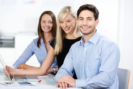 competent: Confident competent business team consisting of a man and twp women sitting smiling at the camera in the office