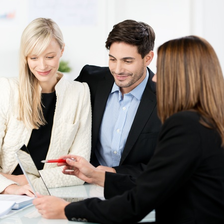 brokers: Attractive stylish young couple in a meeting with a business adviser or estate agent who is making a presentation Stock Photo