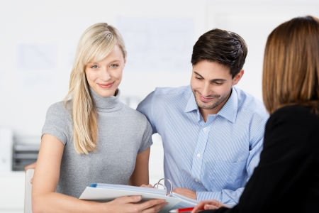agente comercial: Atractiva pareja joven y elegante mirando el papeleo en una carpeta grande durante una reunión con un asesor de negocios