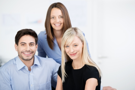 portait: Portait of three male and female business colleagues posing in a group looking at the camera with friendly smiles Stock Photo