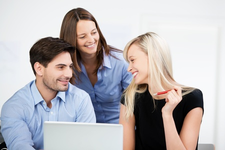 competent: Three young male and female colleagues at the office having a chat sitting around a laptop computer smiling and laughing