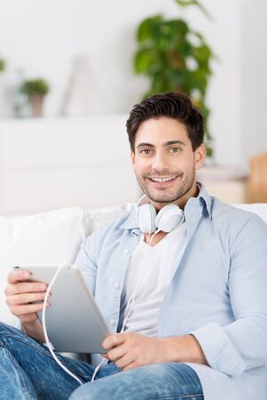 Smiling handsome young man listening to music on his tablet computer relaxing in a comfortable chair at home photo