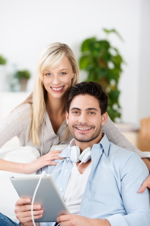 Attractive young couple relaxing in their living room listening to music on a tablet pc through headphones photo