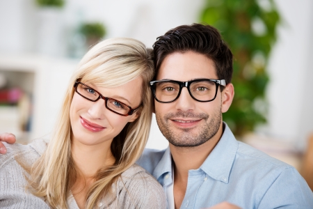 man with glasses: Attractive young couple wearing modern glasses sitting side by side smiling at the camera Stock Photo