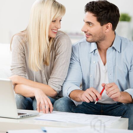 Young couple having a discussion sitting close together on a sofa smiling at each other with an open laptop and paperwork in front of them Stock Photo - 21246681
