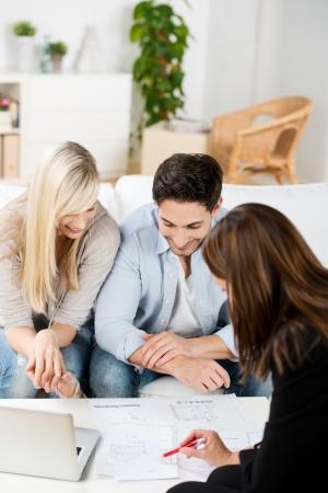 Jong koppel in een zakelijke bijeenkomst bespreken van een project of presentatie met een vrouwelijke adviseur zittend rond een lage tafel in hun woonkamer