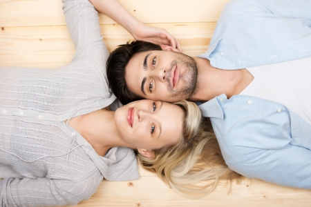 Affectionate young couple lying head to head on their backs on a wooden floor with their cheeks touching, overhead head and shoulders portrait photo