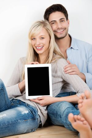 Smiling attractive casual young couple displaying a blank tablet-pc screen towards the viewer while relaxing barefoot on a wooden floor in jeans photo