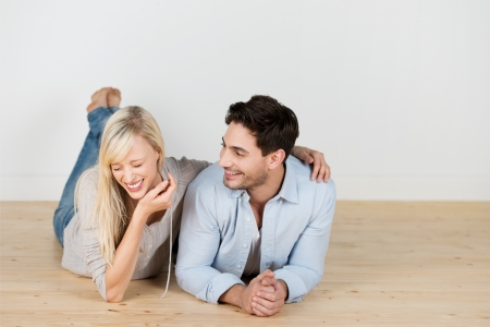 Candid photograph of a laughing young couple lying on the wooden floor side by side facing the camera photo