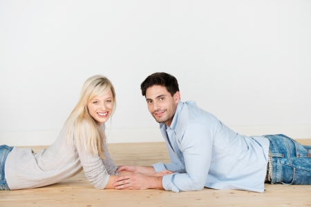 Happy beautiful young couple relaxing at home lying on the wooden floor head to head and holding hands while looking at the camera photo