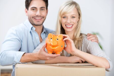 removals: Smiling attractive young couple with a cute orange piggy bank leaning on a brown cardboard removals packing carton as they celebrate their ability to buy a new home through saving
