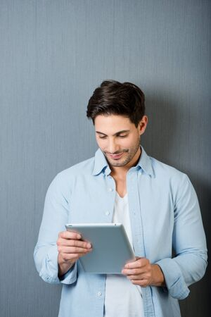 man looking down: Casual unshaven young man working on a tablet-pc standing in front of a grey background with copyspace