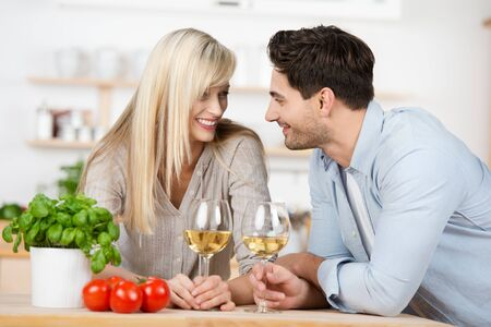 courting: Loving young couple enjoying a glass of white wine in the kitchen leaning on the counter staring into each others eyes with tenderness Stock Photo