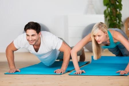 haciendo ejercicio: Atractiva pareja joven atl�tica haciendo flexiones en un gimnasio en colchonetas en un concepto de salud y bienestar Foto de archivo