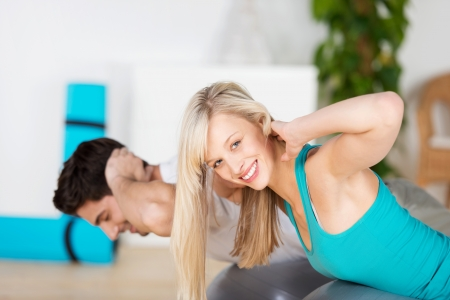 strengthen: Beautiful blond woman doing fitness training in the gym with her husband using a pilated ball to do body lifts to strengthen her muscles, turning to smile at the camera