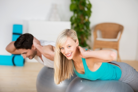 exercise room: Young couple exercising in the gym doing balancing exercises on pilates balls to strengthen their muscles with the beautiful blond woman looking up to smile at the camera