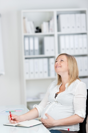Portrait of happy pregnant businesswoman with hands on belly sitting in office photo