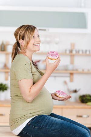pregnant women donuts: Happy young pregnant woman holding donuts while sitting on kitchen counter at home