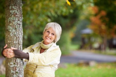 Smiling Senior Frau mit Baumstamm im Park Standard-Bild - 21246761