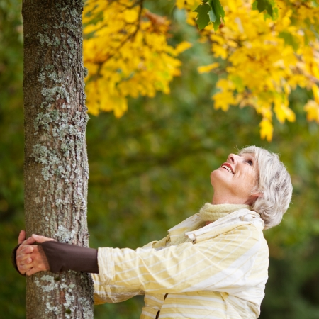 Happy senior woman holding tree trunk while looking up in park photo