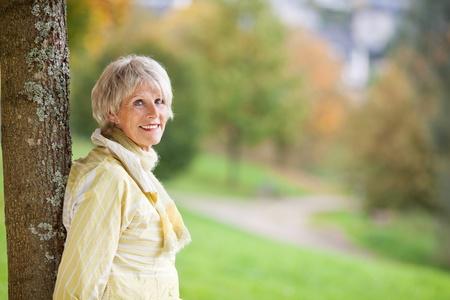 elder tree: Portrait of senior woman leaning on tree trunk in autumn at park
