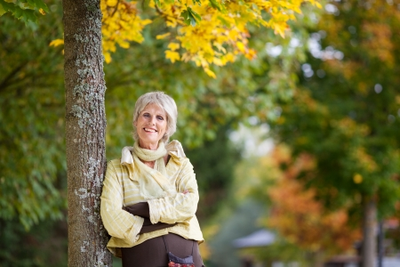 Portrait of smiling senior woman leaning on tree trunk in autumn at park photo
