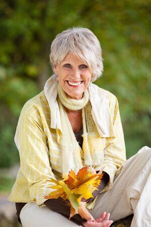 elder tree: Happy senior woman holding yellow autumn leaves at park Stock Photo