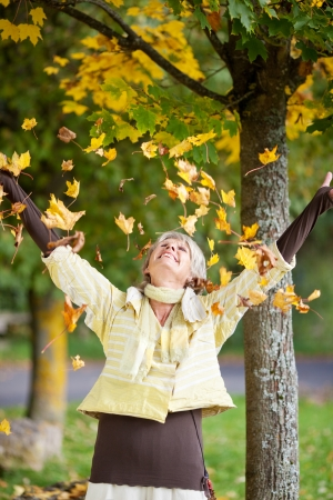 fall fun: Autumn leaves falling on senior woman at park