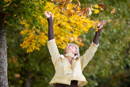 exuberant: Autumn leaves falling on happy senior woman at park