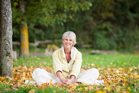 wellness woman: Happy senior woman relaxing in autumn at park Stock Photo