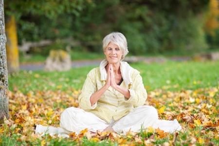 Senior vrouw met gevouwen handen glimlachen tijdens het mediteren in het park