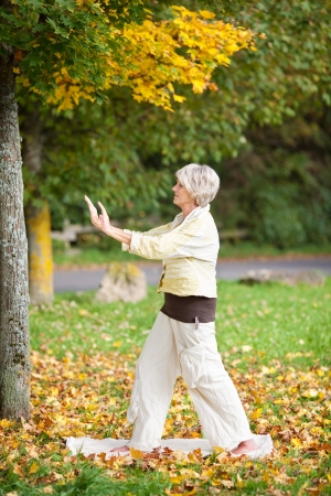 Profile shot of senior woman with arms raised doing yoga in park photo