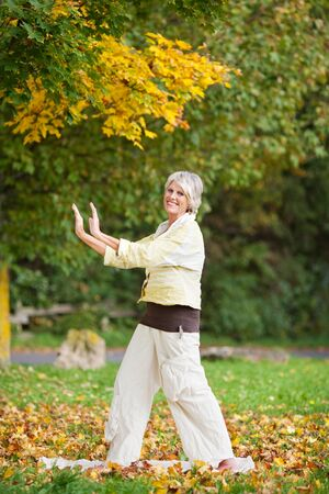 tai chi: Smiling senior woman with arms raised doing yoga in park Stock Photo