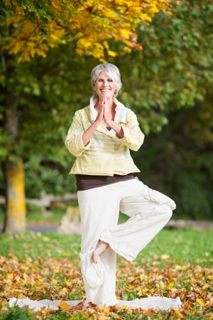 Full length of smiling senior woman with arms outstretched standing on one leg while doing yoga in park