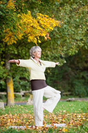 serene people: Full length of senior woman with arms outstretched standing on one leg while doing yoga in park