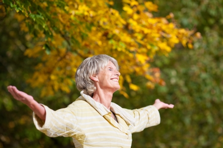 Senior woman with arms outstretched enjoying nature in park photo