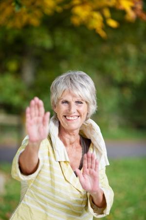 Portrait of senior woman performing Tai Chi in park photo