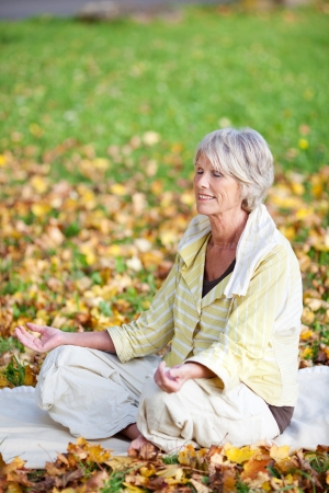 Low section of senior woman with eyes closed meditating in lotus position at park photo