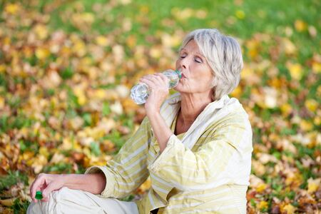 Senior woman with eyes closed drinking water while sitting in park photo